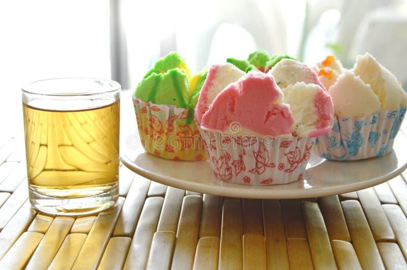 Blandad färgrik bomullsmuffin i papper på maträtt och te fotografering för bildbyråer