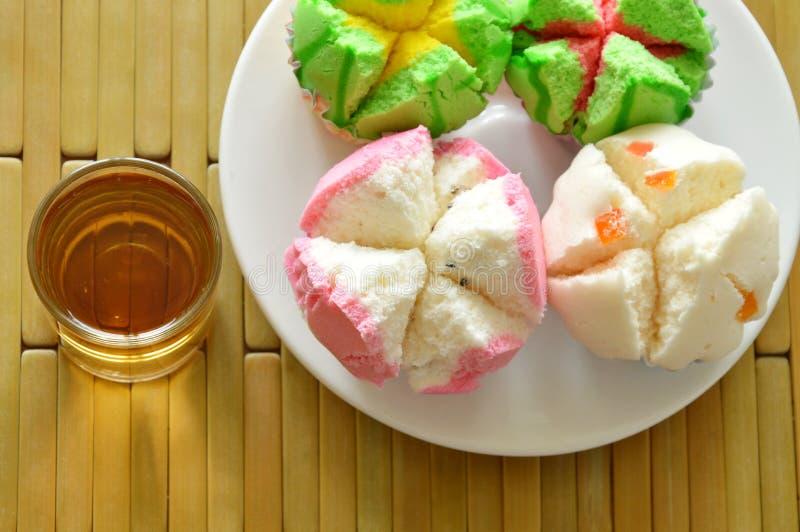 Blandad färgrik bomullsmuffin i papper på platta- och tekoppen royaltyfria foton