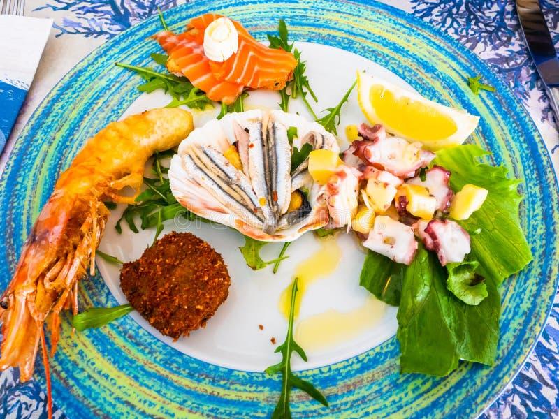 Blandad fisk för havs- maträtt, bläckfisksallad, stekt röd räka, ansjovis arkivfoton