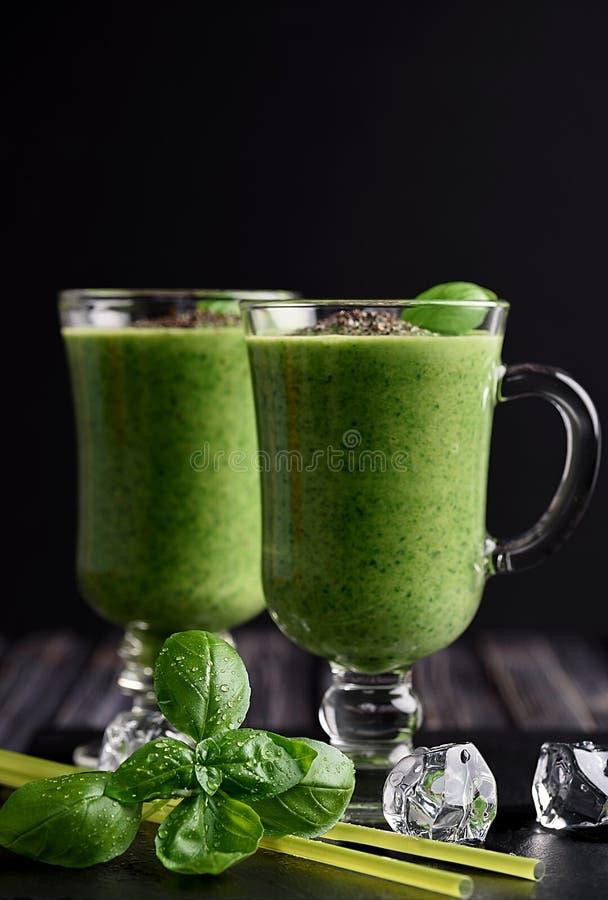 Blandad grön smoothie med ingredienser på trätabellen arkivfoto
