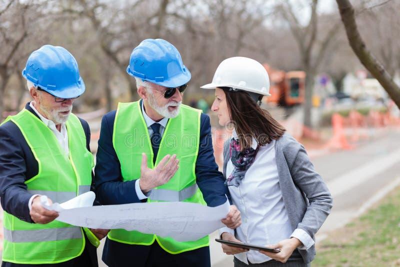 Blandad grupp av arkitekter och affärspartners som diskuterar projektdetaljer på en konstruktionsplats arkivbild