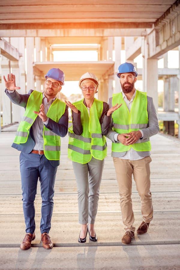 Blandad grupp av arkitekter som går till och med fabrikstillverkad delarna till konkret konstruktionsplats som kontrollerar arbe royaltyfri foto