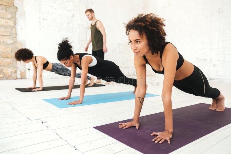 Blandad grupp av ungdomarsom gör yogagrupp arkivbild