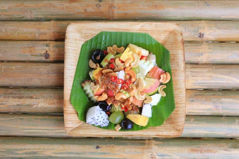 Blandad kryddig fruktsallad som tjänas som på bananbladet på bambuträtabellen, thailändsk mat royaltyfri bild