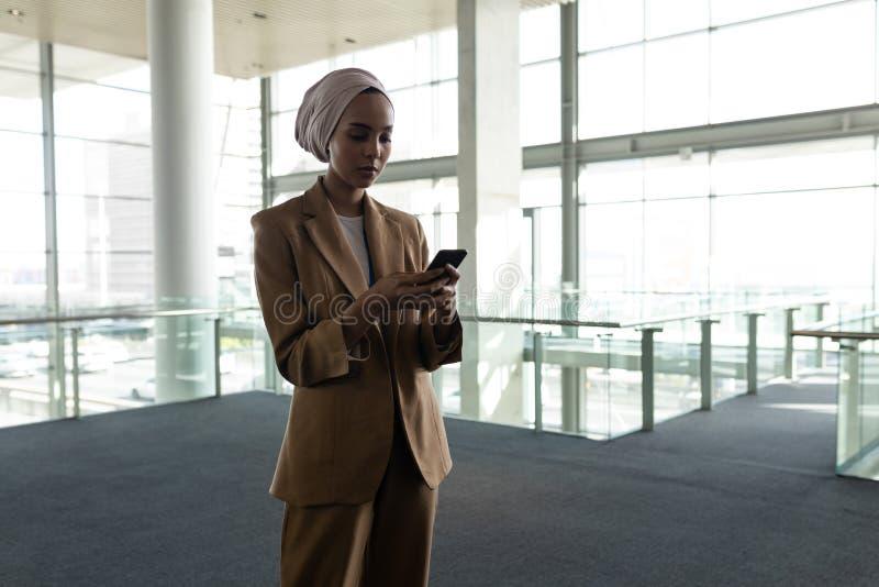 Blandad-lopp affärskvinna som i regeringsställning använder lobbyen för mobiltelefon arkivfoto