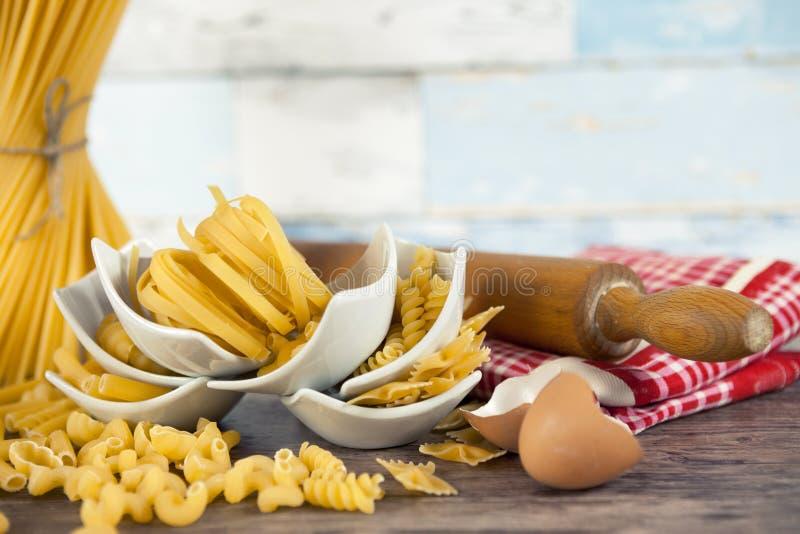 Blandad pasta i liten vit bowlar med kavlen arkivfoton