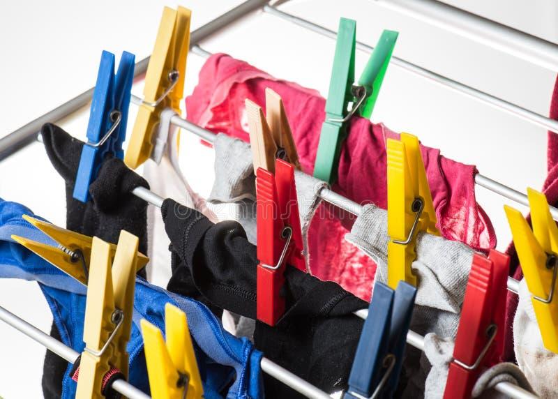 Blandad ren tvätteri som klämmas fast med färgglade klädnypor royaltyfri bild
