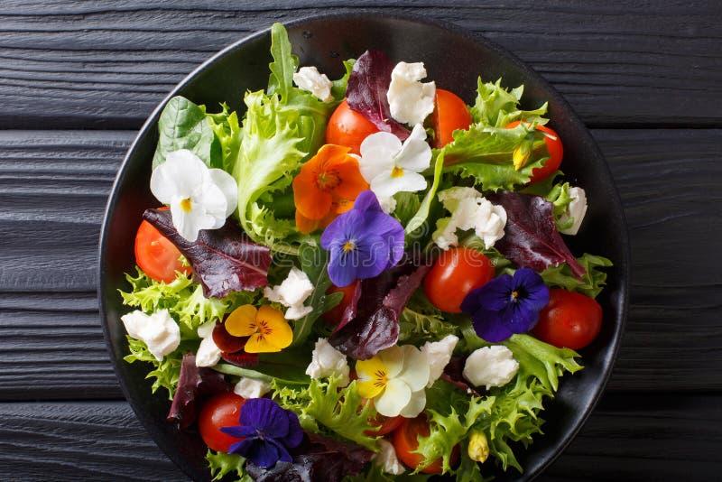 Blandad sallad av ätliga blommor med grönsallat, tomater och kräm c royaltyfria foton
