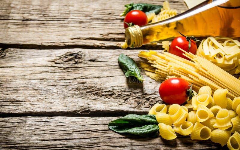 Blandad torr pasta och spagetti, med tomater, örter och olivolja arkivfoto