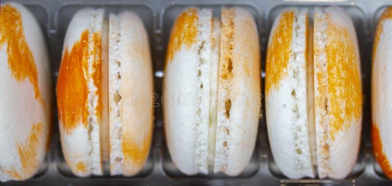 Blandade den gula vita apelsinen för den franska raden för makaroni vertikala Två färgmakron med kräm Aptitretande härliga sötsak arkivfoto