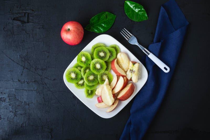 Blandade den nya kiwin och äpplen för frukt med druvor i en platta på en trätabell fotografering för bildbyråer