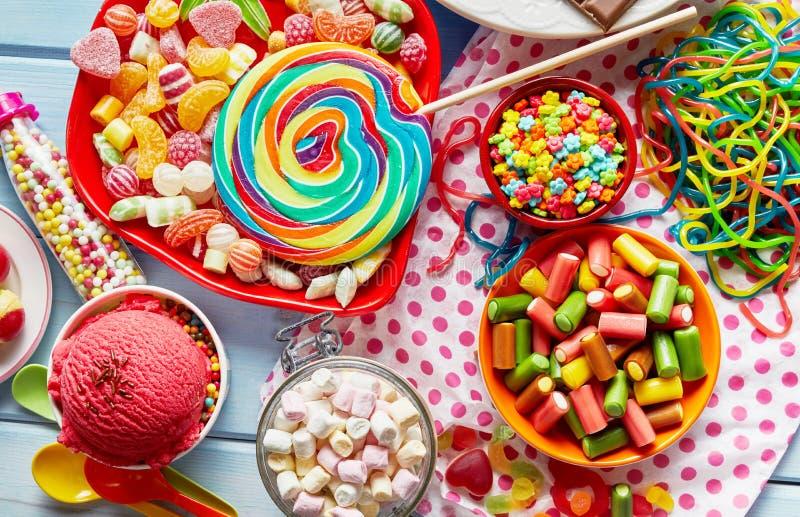Blandade färgglade ungar festar sötsaker och godisen arkivbild