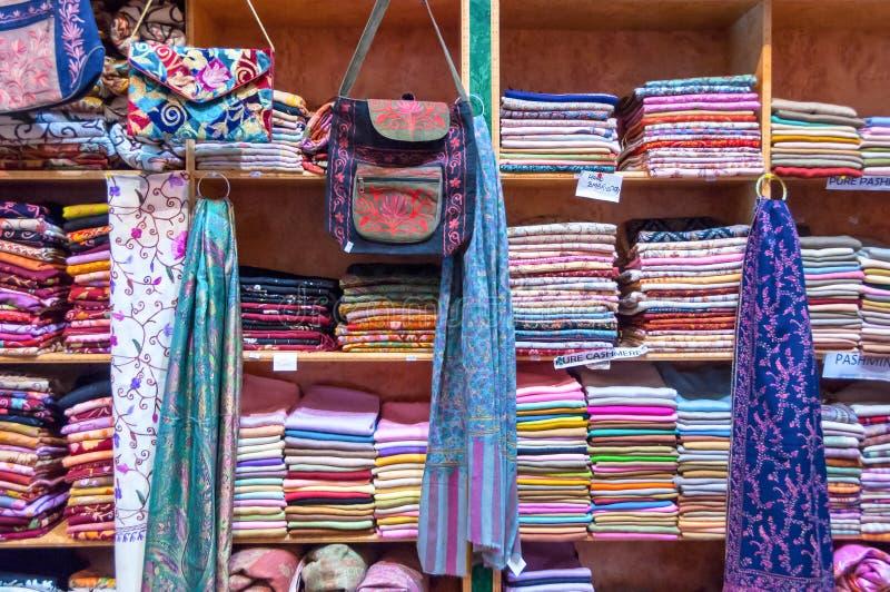 Blandade färgrika tyger på skärm i en shoppa Muttrah Souk, i Mutrah, Muscat, Oman, Mellanösten arkivbilder