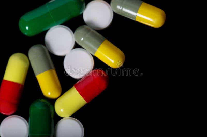 Blandade farmaceutiska medicinpreventivpillerar, minnestavlor och kapslar över svart bakgrund arkivbilder