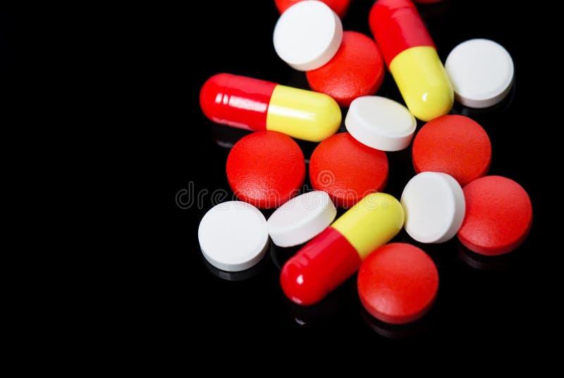 Blandade farmaceutiska medicinpreventivpillerar, minnestavlor och kapslar över svart bakgrund royaltyfria bilder