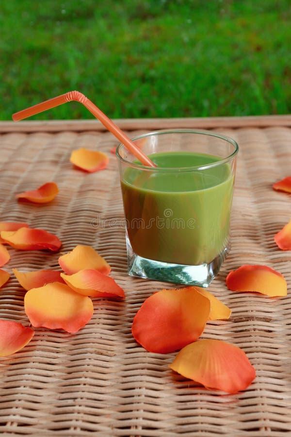 Blandade gröna smoothie- och blommakronblad på tabellen arkivbild