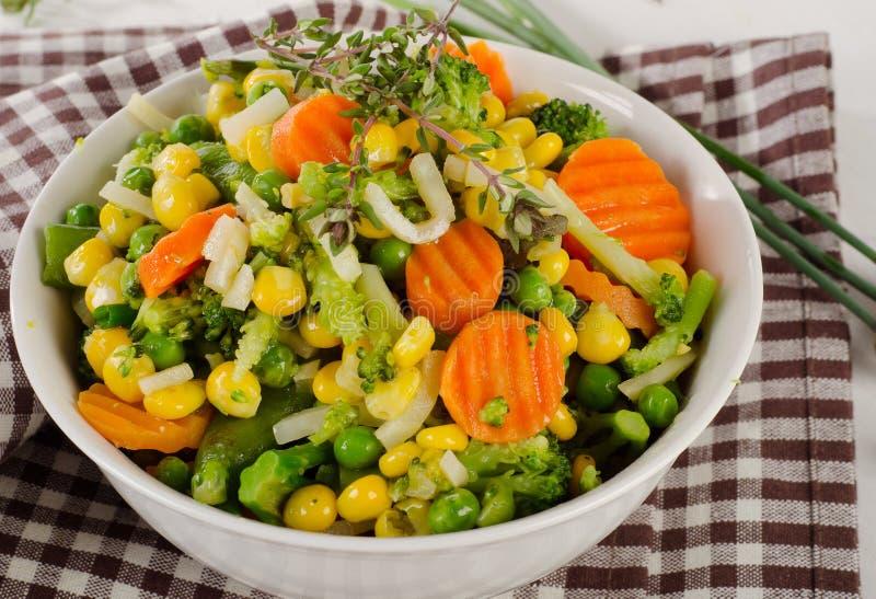 Blandade grönsaker med nya örter i en vit bunke royaltyfri fotografi