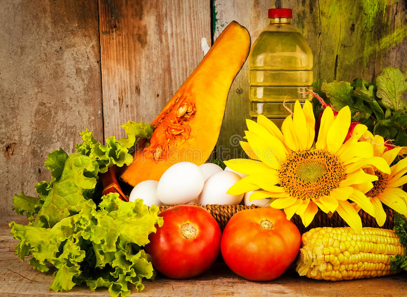 Blandade grönsaker och solrosor på en korg arkivbild