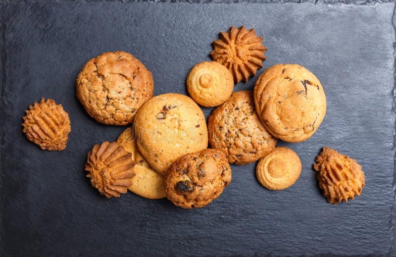 Blandade kakor med chokladchipen, havremjölrussin på stenen kritiserar upp bakgrund på träbakgrundsslut stekhett hemlagat royaltyfria foton