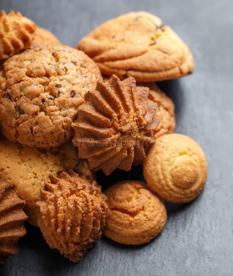 Blandade kakor med chokladchipen, havremjölrussin på stenen kritiserar upp bakgrund på träbakgrundsslut stekhett hemlagat royaltyfri fotografi