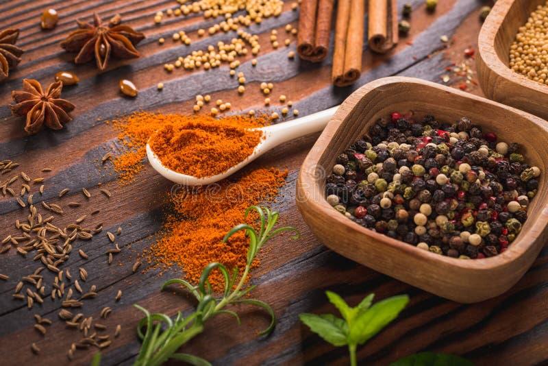 Blandade kryddor och örter i köksgeråd arkivbilder