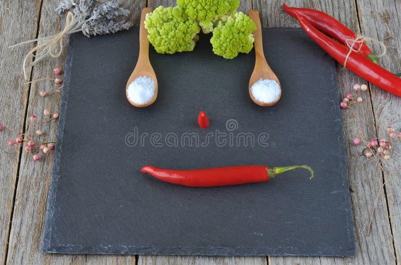 Blandade kryddor och smaktillsatser på stenen, kritiserar och träbakgrund Varma peppar och blomkål royaltyfria bilder