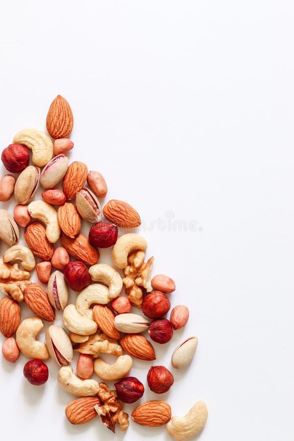 Blandade muttrar på en vit tabell Hasselnötter kasjuer, jordnötter, valnötter, mandlar arkivfoto