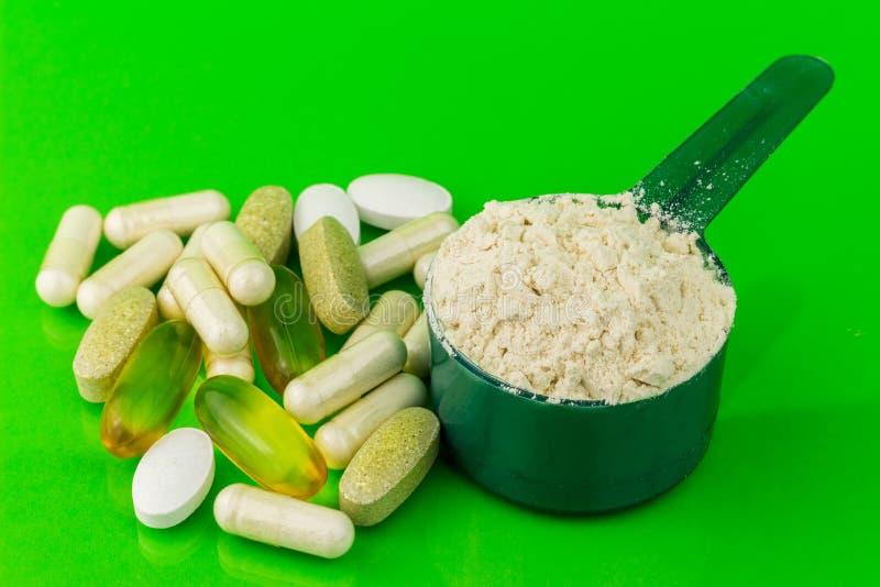 Blandade naturliga mattilläggpreventivpillerar och proteinpulver i plast- sked på grön bakgrund royaltyfri fotografi