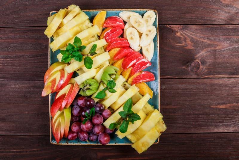 Blandade nya frukter på plattan Apple, druvor, kiwi, ananas, grapefrukt, apelsin, banan och mintkaramell på trätabellen royaltyfri foto