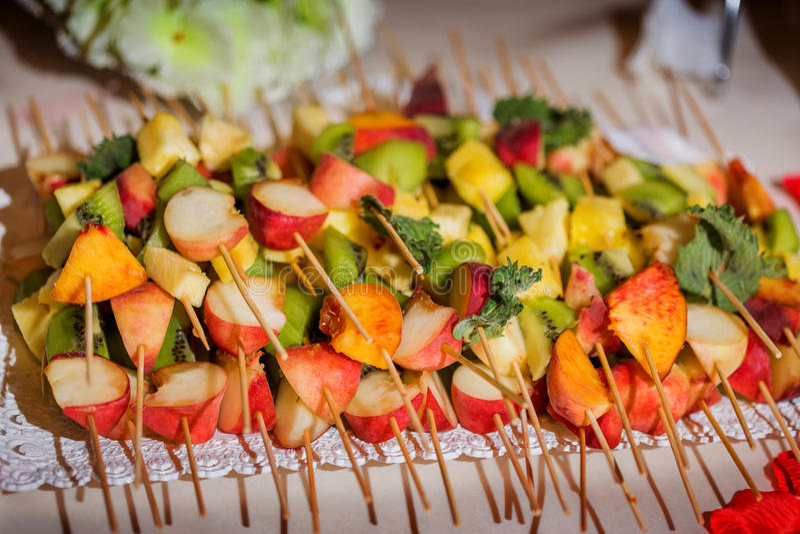 Blandade nya frukter på steknålar på tabellen, närbild fotografering för bildbyråer