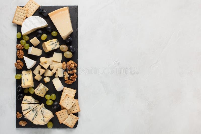 Blandade ostar med vita druvor, valnötter, smällare och på en sten stiger ombord Mat för ett romantiskt datum på en ljus bakgrund royaltyfria foton