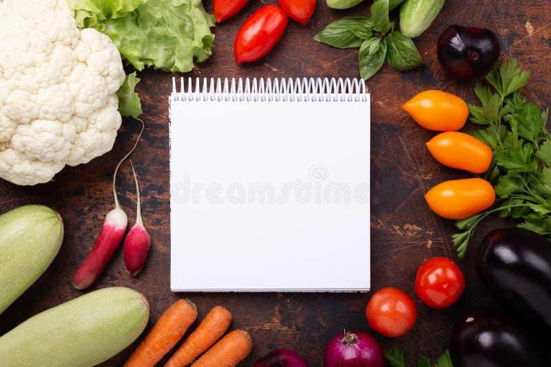 Blandade rå organiska grönsaker och anteckningsbok på träbakgrund arkivfoto