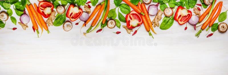 Blandade rå organiska grönsaker och ingredienser för sund matlagning på vit träbakgrund, bästa sikt, baner arkivfoto