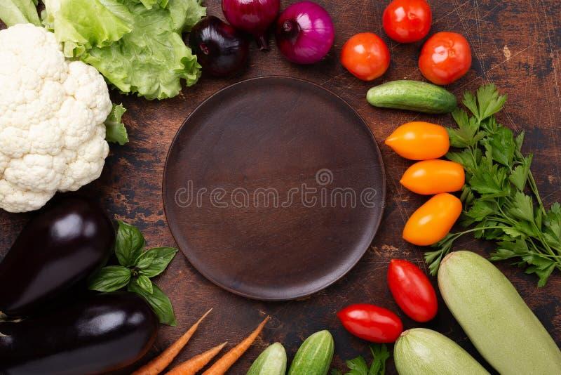 Blandade rå organiska grönsaker och tom platta på mörkerstenbakgrund arkivbild