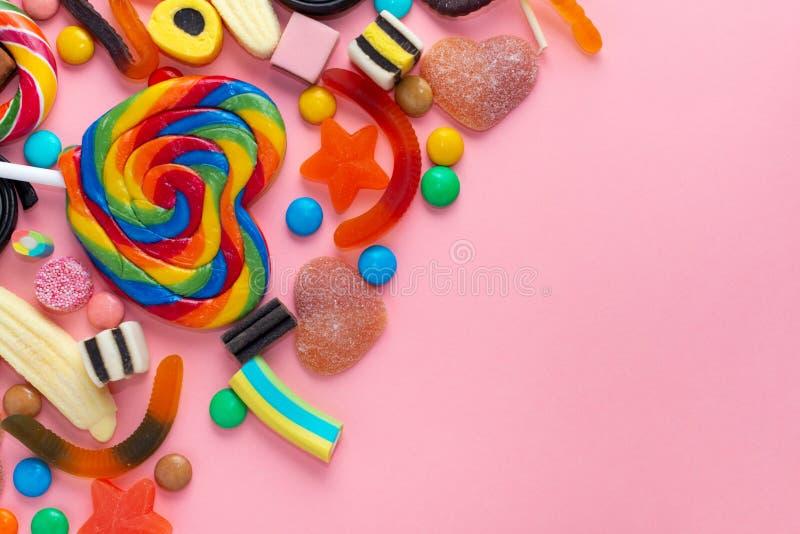 blandade sötsakklubbor och godisar över rosa färger som festlig bakgrund med kopieringsutrymme royaltyfria bilder