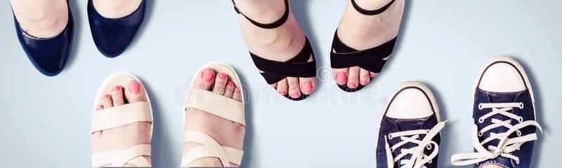 Blandade skor för sommarkvinna` s Kvinnlig fot i sandaler, gymnastikskor, skor arkivfoton