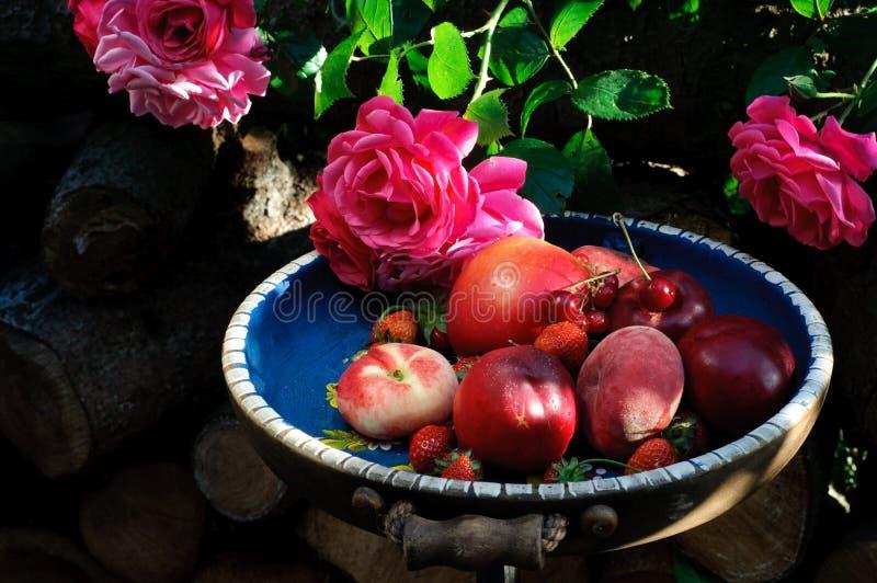 Blandade sommarfrukter och rosor royaltyfria foton
