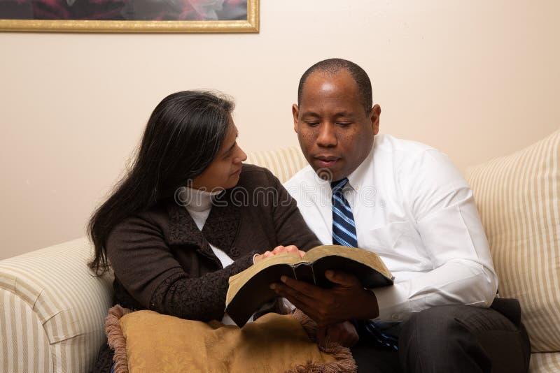 Blandade sprang Christian Couple Studying Bible Together fotografering för bildbyråer