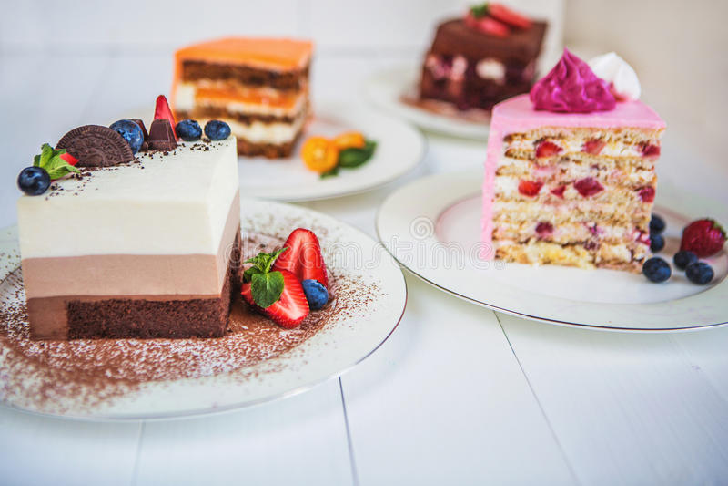 Blandade stora stycken av olika kakor: tre choklad, morot, jordgubbe, choklad Kakor dekoreras med bär royaltyfria foton