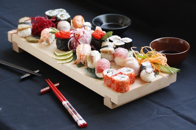 Blandade typer av sushi på bambutabellen med hashipinnar och shoyu arkivfoto