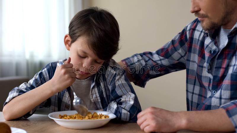 Blandande cornflakes för ledsen manlig unge med skeden, fader som slår barnet, fattig aptit arkivfoto