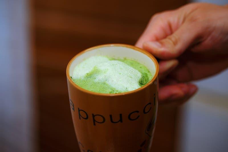 Blandande grönt pulver för korngräs i manhand Fruktsaft för vitalitet fotografering för bildbyråer