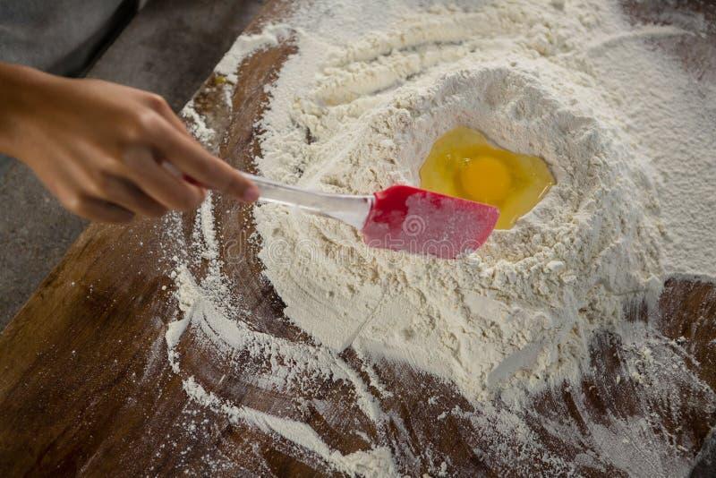 Blandande mjöl och ägg för kvinna med en smetspatel royaltyfri fotografi
