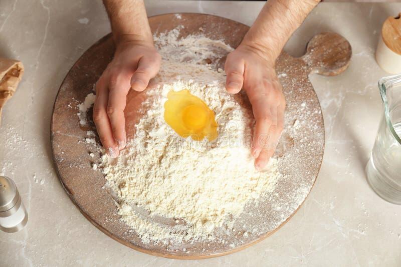 Blandande mjöl och ägg för man royaltyfria bilder