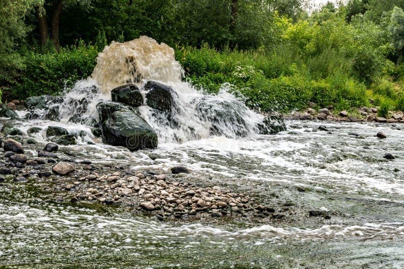 Blandande zon av avloppsledning av stads- kloak Flodf?rorening Stadsf?rr?dsplatser konstgjord geyser exponering long arkivfoton