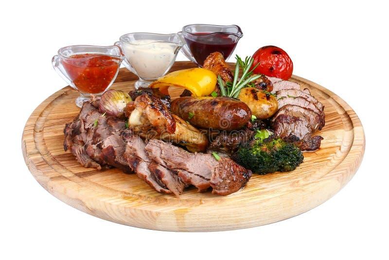 Blandat grillat kött med bakade grönsaker på ett träbräde arkivbild