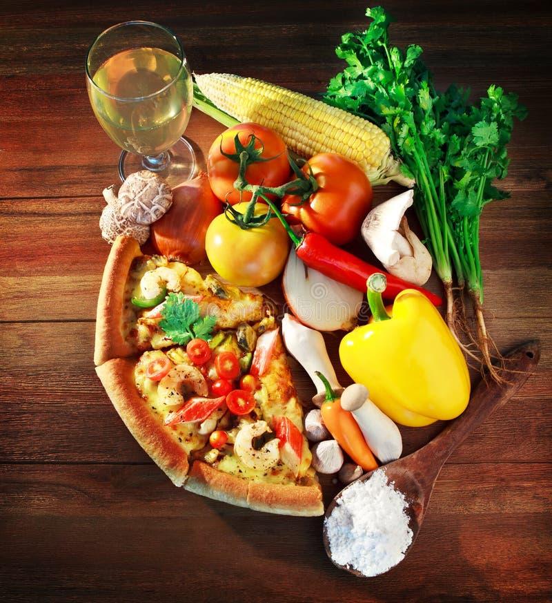 Blandat innehåll och vegatable med stycken av pizza för havsmat på wo royaltyfria bilder