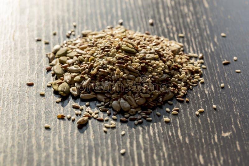 Blandat torrt frö pumpa, sesam, solros, lin för sunt äta på den träsvarta tabellen royaltyfri bild