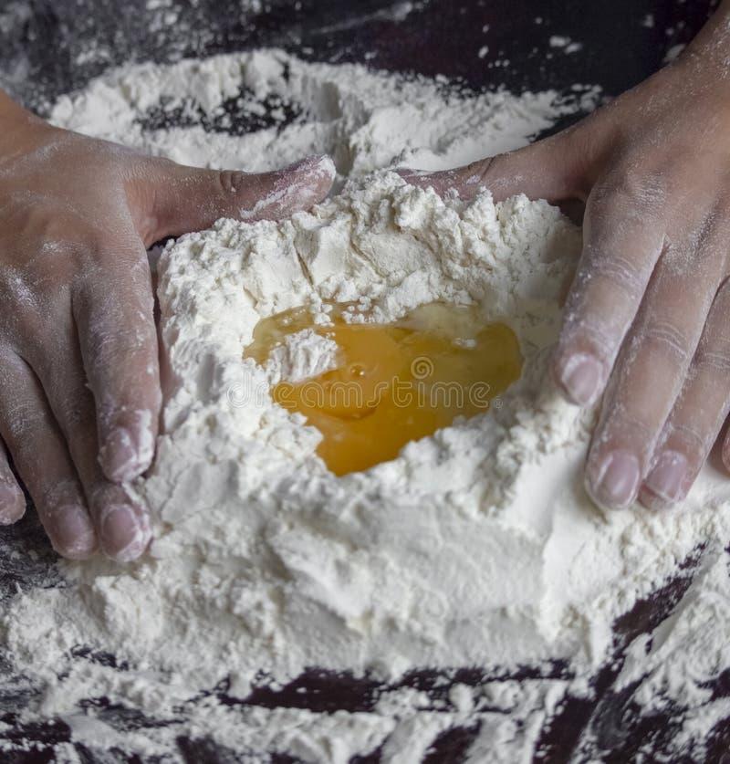 Blandning av ett ägg med mjöl, degförberedelse arkivfoton