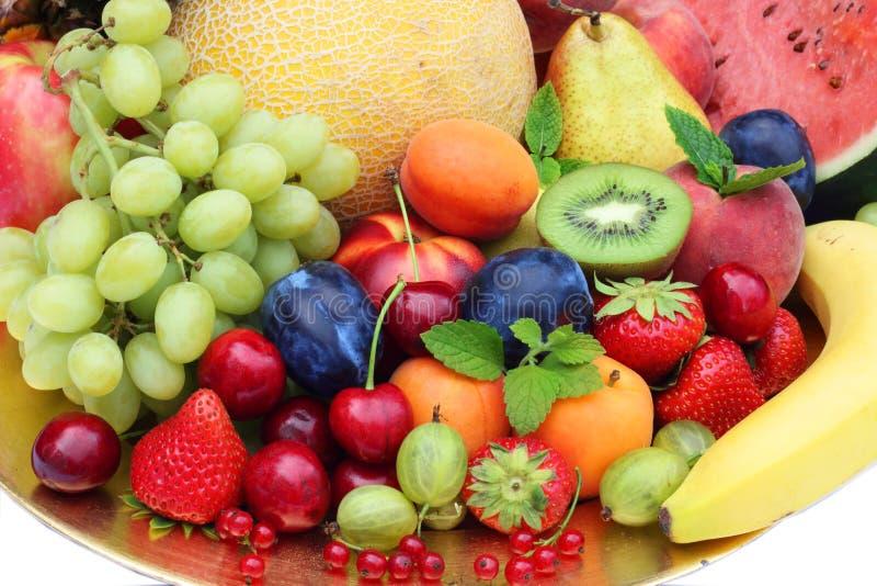 Blandning av frukter och grönsaker på den guld- plattan royaltyfri fotografi